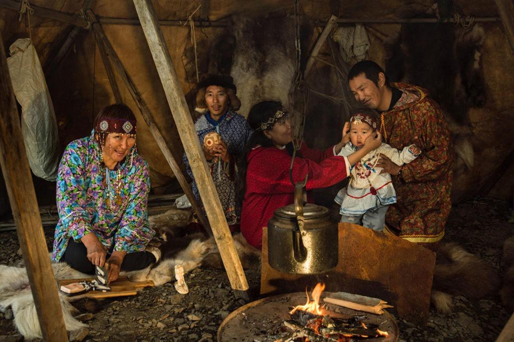 Вокруг очага — семья Выквырагтыргыргыных, что в переводе означает «возвращающийся домой камнем». Когда-то мать главы семейства, будучи в положении, ушла с утра на рыбалку. Там, на берегу, и родился Валера. Он вырос и стал резчиком и гравером по бивню моржа и мамонта. Его жена Лариса — хранительница семейных традиций. Она обучила чукотскому языку и фольклору своих сыновей, а сейчас напевает песни своим внучкам. Фото: предоставлено АНО «Общественный продюсерский центр»/Олег Зотов/Ида Ручина